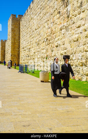 JERUSALEM, ISRAEL - APRIL 29, 2016: Ultra-Orthodox Jews and other visitors, near Jaffa gate, part of the walls of - Stock Photo