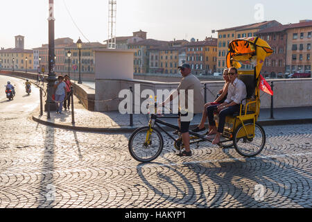 unidentified people on a cycle rickshaw riding over an Arno Bridge in Pisa - Stock Photo