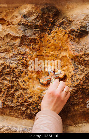 A pilgrim blesses a cross with Jesus hand print, in Via Dolorosa station 5, on Orthodox Good Friday, in the old - Stock Photo