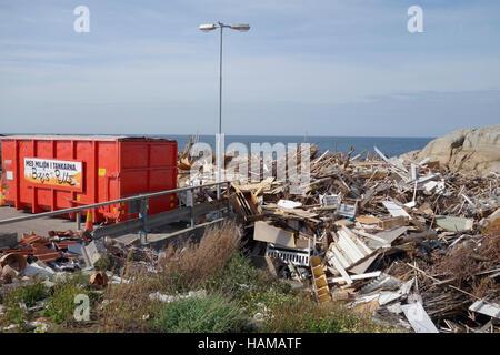Dumping ground for discarded wood on the coast of Öckerö island, Bohuslan, Sweden - Stock Photo