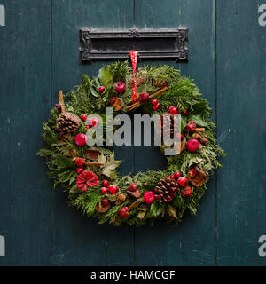 Advent Christmas wreath on wooden door decoration - Stock Photo