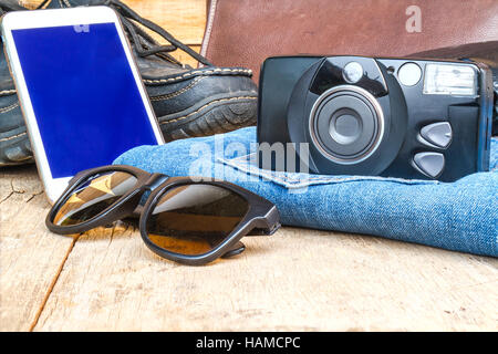 Travel casual outfits with camera, smartphone, shoes, wallet, leather bag, sunglasses and jean on wooden table. - Stock Photo