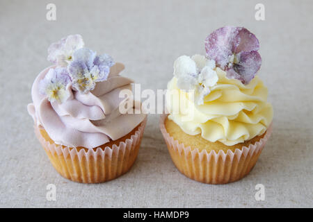 Purple and yellow cupcakes with sugared edible flowers on linen background - Stock Photo