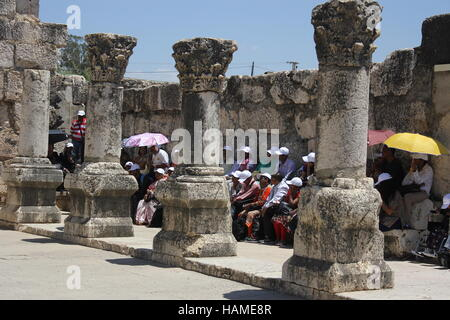 A tour group listens to the teaching of a priest while in the ruins of the synagogue where Jesus taught. Capernaum, - Stock Photo