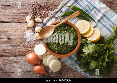 Green spicy sauce chimichurri and ingredients close-up on the table. horizontal view from above - Stock Photo