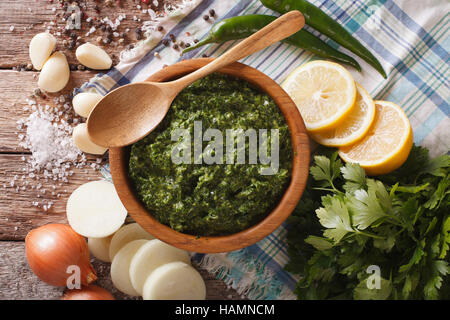 Argentine chimichurri sauce with ingredients close-up on the table. Horizontal view from above - Stock Photo