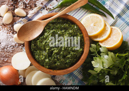 Chimichurri sauce with ingredients close-up on the table. horizontal view from above - Stock Photo