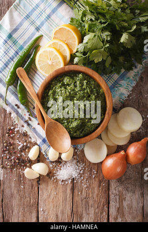 Argentine chimichurri spicy sauce and ingredients close-up on the table. vertical view from above - Stock Photo