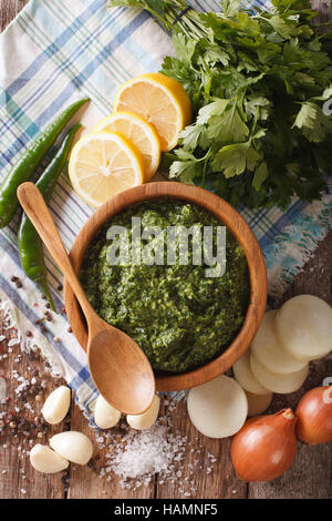 Argentine chimichurri sauce with ingredients close-up on the table. vertical view from above - Stock Photo