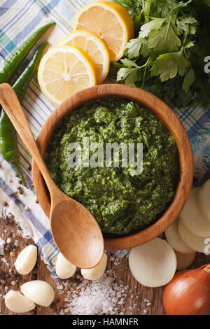 Chimichurri sauce with ingredients close-up on the table. vertical view from above - Stock Photo