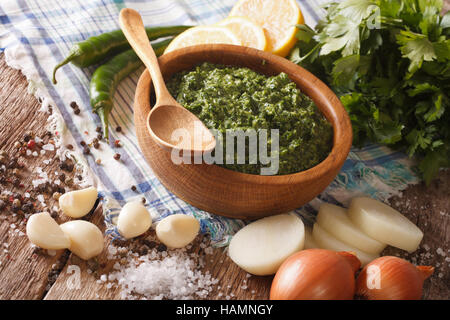 Green spicy sauce chimichurri and ingredients close-up on the table. horizontal - Stock Photo