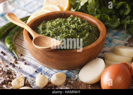 Argentine chimichurri spicy sauce and ingredients close-up on the table. horizontal - Stock Photo