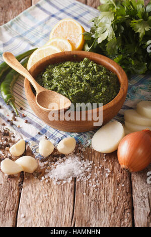 Argentine chimichurri sauce and freshly prepared ingredients close-up on the table. vertical - Stock Photo