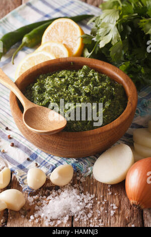 Argentine chimichurri sauce with ingredients close-up on the table. vertical - Stock Photo