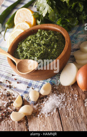 Chimichurri sauce with ingredients close-up on the table. vertical - Stock Photo