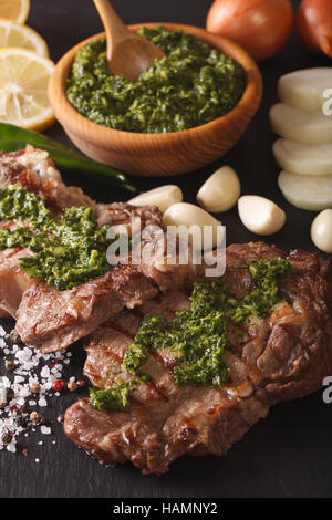 Argentine cuisine: grilled beef steak with chimichurri sauce macro on the table. Vertical - Stock Photo
