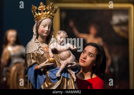 London, UK.  2 December 2016.  A staff member views a 14th century Madonna and Child sculpture (est. 60-80k), at - Stock Photo