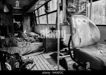 A group of travelers sleep inside an old bus transformed into a hostel - Stock Photo
