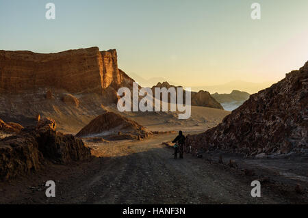 A traveler walks along an unpaved road next to his bike at sunrise through the middle of the Moon Valley in the - Stock Photo