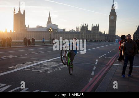 A youth balances on his rear wheel to perform a wheelie on the South side of Westminster Bridge, on 30th November - Stock Photo