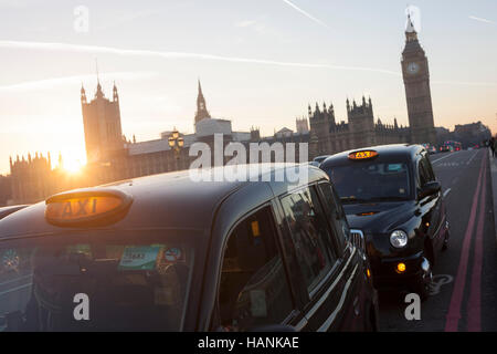 With a setting sun, Big Ben and the Houses of Parliament in the distance, two black London taxies are stopped on - Stock Photo