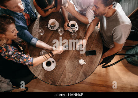 Top view of young people sitting around a cafe table and looking at mobile phone. Young men and women looking at - Stock Photo