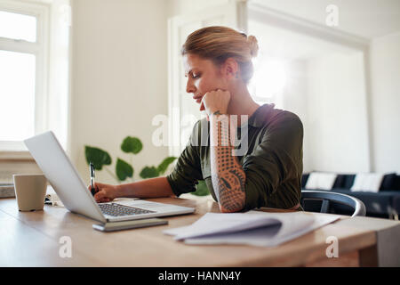 Shot of young woman working at home office. Beautiful female sitting at table with laptop and documents. - Stock Photo