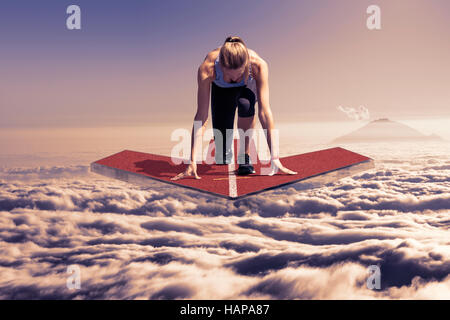 Female runner kneels in start position on a floating red arrow platform, which hovers at late sunset over the clouds - Stock Photo