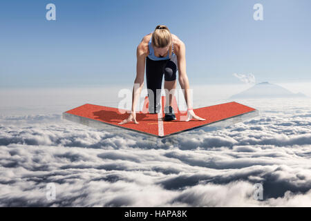 Female runner kneels in start position on a floating tartan arrow platform, which floats above the clouds. - Stock Photo