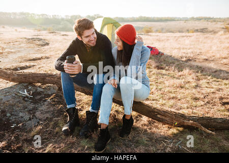 Couple near the tent. sitting on a log - Stock Photo