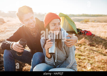Happy couple with tea sitting on log near the tent - Stock Photo