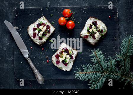 Vegan sandwiches with roasted beet and goat cheese on wooden cutting board, top view - Stock Photo