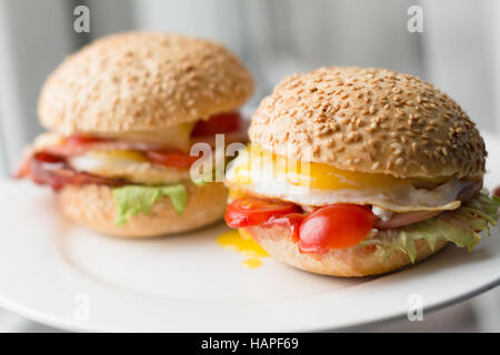 Bacon, egg and tomato sandwiches on white plate, close up view - Stock Photo
