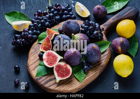 Fresh figs, black grapes and lemons. Fresh fruit variety on wooden cutting board - Stock Photo