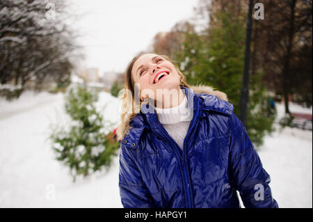 Portrait of young woman against the background a winter landscape. She is dressed in bright blue down-padded coat, - Stock Photo