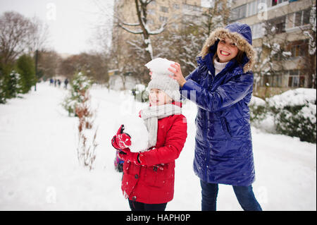 Young woman and her daughter cheerfully spend time on street in winter day. They are dressed in warm jackets. Ground - Stock Photo