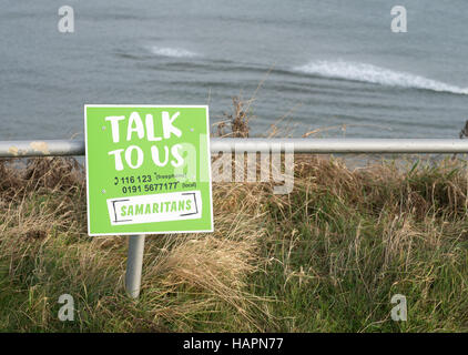 Samaritans sign above sea cliffs Talk To Us, The Leas, South Shields, South Tyneside, England, UK - Stock Photo