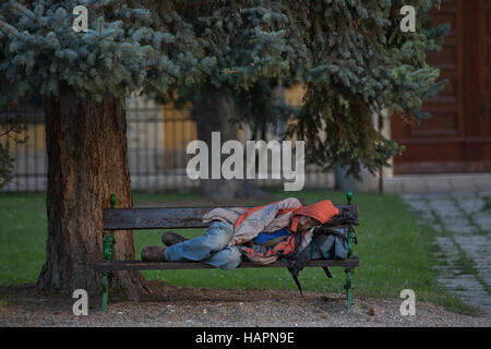 Homeless man sleeping on a bench within the grounds of The Basilica Eger Erlau or Egri Bazilika, Hungary, Europe - Stock Photo