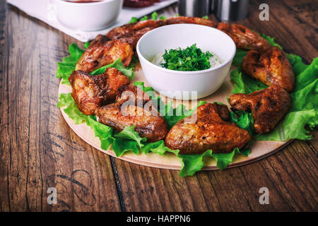 delicious grilled chicken wings with garlic and tomato sauce with lettuce on a round board on wooden rustic background - Stock Photo
