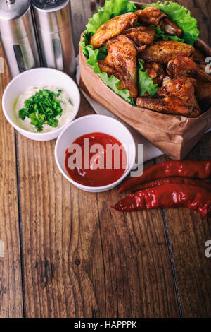 delicious grilled chicken wings with garlic and tomato sauce with lettuce in food paper bag on wooden rustic background - Stock Photo