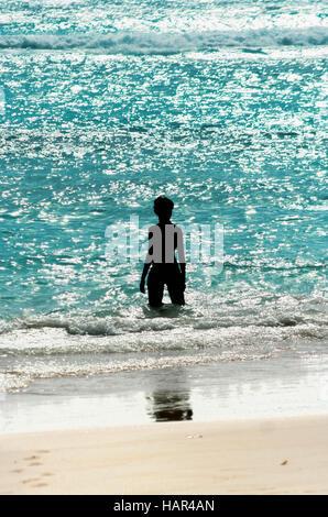 Woman silhouette standing in a shinny warm sea - Stock Photo