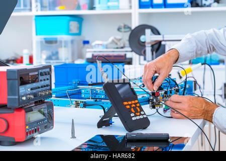 Adjusting an industrial robot with a CNC computer control - Stock Photo