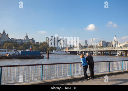 London middle age couple looking on the Hungerford Bridge and Golden Jubilee Bridges - Stock Photo