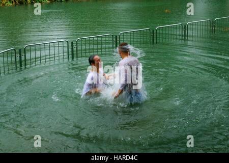 YARDENIT, ISRAEL - JANUARY 19, 2016: Pilgrims baptizing in the Jordan River, in the Yardenit Baptismal Site. Northern - Stock Photo