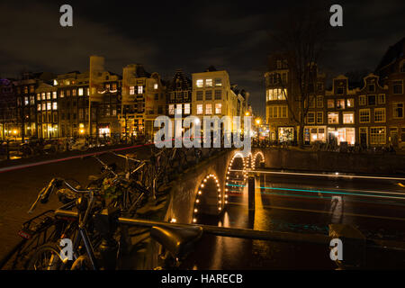 Light trails of cars and boats in the canals of Amsterdam during Amsterdam Light Festival - Stock Photo