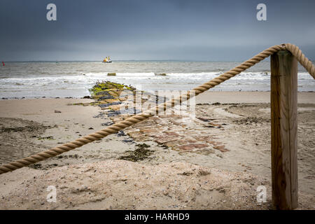 Beach post with rope banister on top and beach in background, Norderney Island, Germany, Europe. - Stock Photo