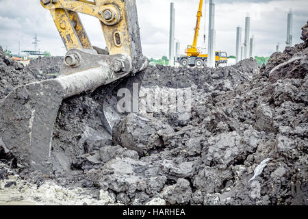Excavator is digging with his bucket against moody sky. - Stock Photo