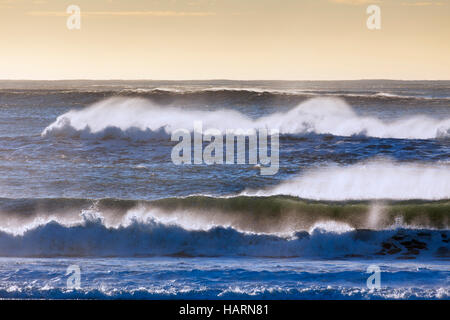 Crests of braking waves at Arctic sea showing airborne spray and spindrift due to high winds - Stock Photo
