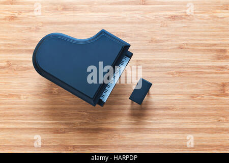 Black toy grand piano on a wooden floor with stool standing near it. Top view. Music concept. - Stock Photo