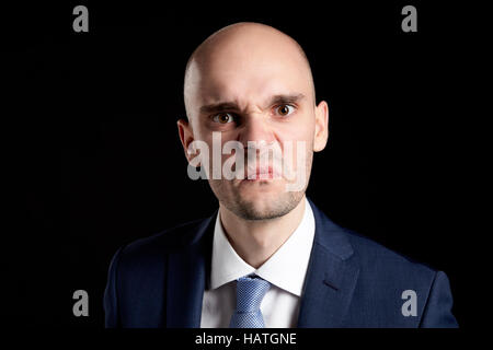 Portrait of Bald Angry Man against Black Background. - Stock Photo